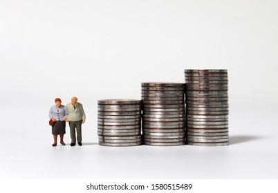 Old age miniature people with a pile of coins.