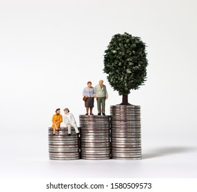 Old age miniature people and a miniature tree on a pile of coins.