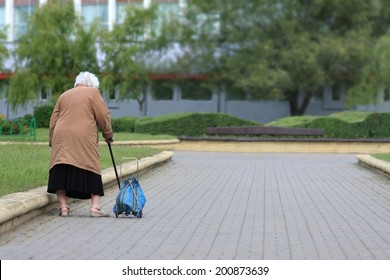Old age - no joy. Old woman with bag seen from behind. Grandmother tired.