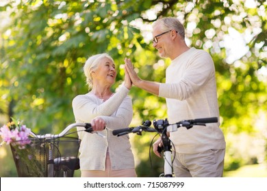 old age, people and lifestyle concept - happy senior couple with fixie bicycles making high five at summer city park