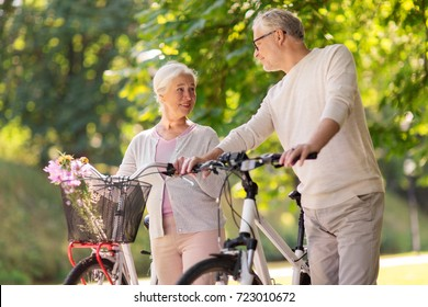 old age, people and lifestyle concept - happy senior couple walking with fixie bicycles talking at summer city park