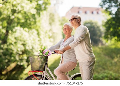old age, people and lifestyle concept - happy senior couple with fixie bicycle at summer city park
