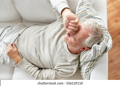 old age, problem and people concept - close up of tired senior man lying on sofa at home