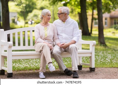 old age, relationship and people concept - happy senior couple sitting on bench at summer park