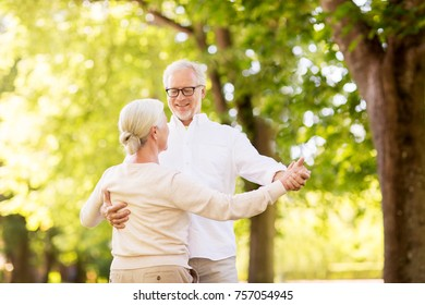 old age, relationship and people concept - happy senior couple dancing waltz at summer park