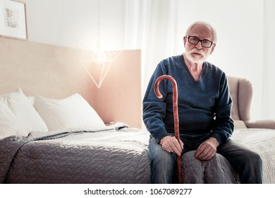 Old age. Serious nice elderly man sitting on the bed an holding his walking stick while resting at home