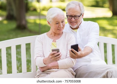 old age, technology and people concept - happy senior couple with smartphones at summer park