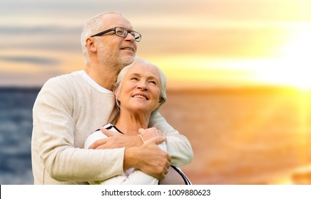 old age, tourism, travel and people concept - happy senior couple over sunset background