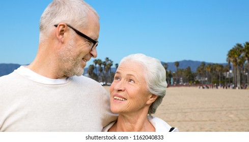 old age, travel and tourism concept - happy senior couple hugging over venice beach background in california