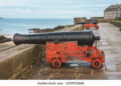 Old aged cannons on red wooden carriages facing the sea on ancient fortification ramparts of Saint-Malo, Brittany, France