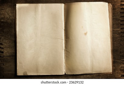 old aged open book with blank pages sitting on antiqued wood