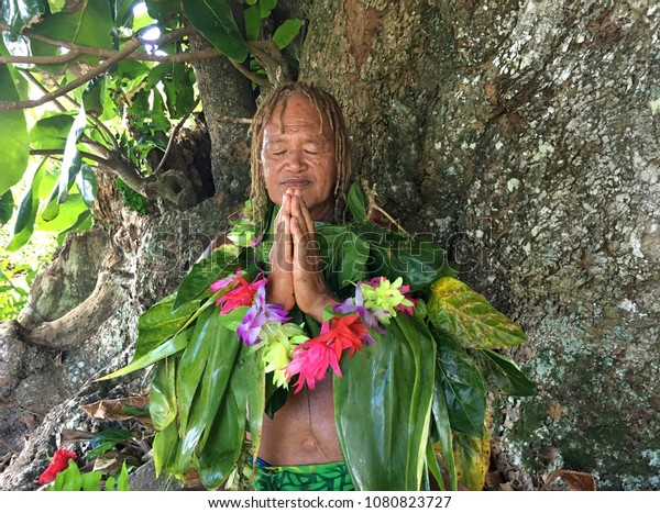 An old aged Pacific Islander man praying under a rain forest tree in Rarotonga, Cook Islands. Real people Copy space
