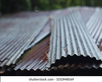 old aged weathered rusty galvanized corrugated iron sheet roof of a poor man's hut sad and abandoned mood selective focus blur background