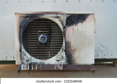 Old air condition that is damaged from the fire. The air conditioner is broken because of short circuit or Causing a new mark that shrunken black on the body On a white background and cement floor.