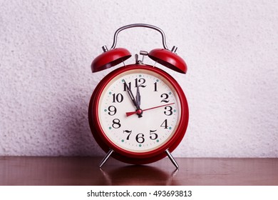 Old alarm clock with five minutes to twelve o'clock