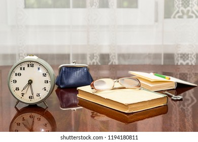 old alarm clock, old glasses, a wallet book, a pencil on a polished table and a white curtain