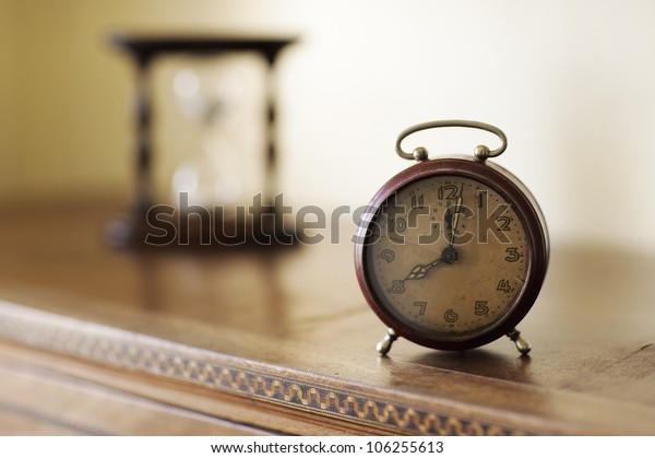 old alarm clock with hourglass on background, copy space