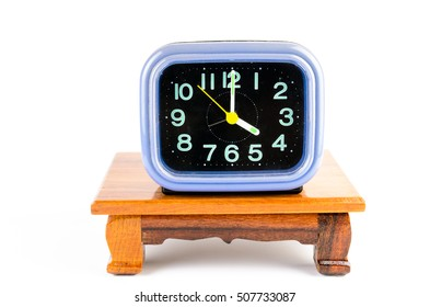 Old alarm clock on wooden table isolated on the background