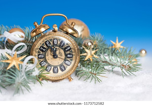 Old alarm clock set to five to twelve on Christmas fir twigs with snow and balls