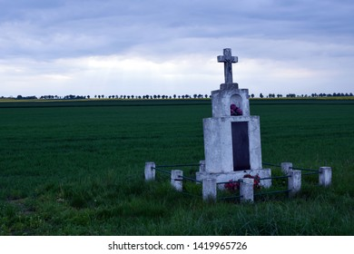 Old alone memorial cross between fields. Remember of tragic dead.