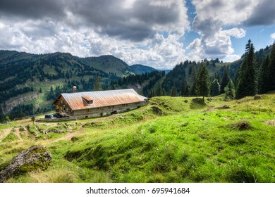 Old alpine hut with meadow in the Alps. Bavaria, Allgau, Germany. Traditional agriculture in the mountains.