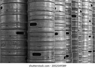 Old Aluminum Beer keg. Wall of used and scratched stainless steel beer barrels or kegs. Stacked in a row large silver or metallic colour alcohol barrels or containers.