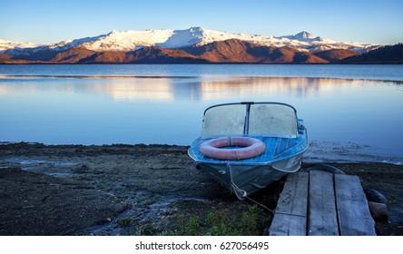 Old aluminum boat with lifebuoy on autumn shore of the lake Markakol, Altai mountains East Kazakhstan.