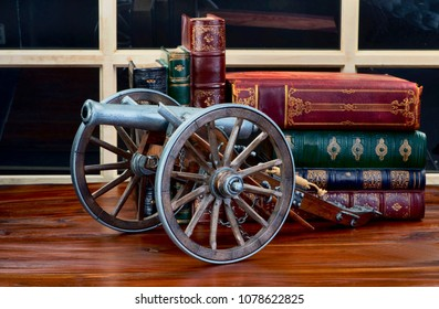 Old American artillery model with antique literature in the background.