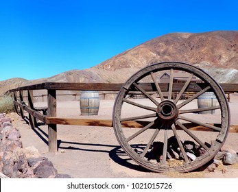 Old American farm in the desert, with fence and a wheel of carriage