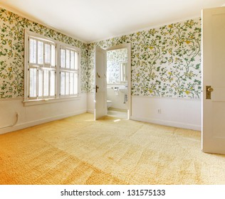 Old American house bedroom interior with wallpaper and carpet.
