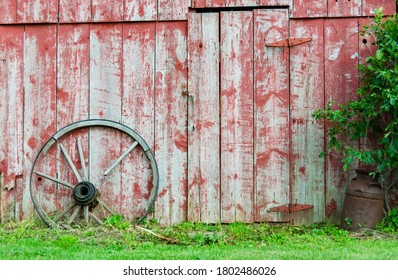 Old Amish barn with broken wagon wheel leaning against it.