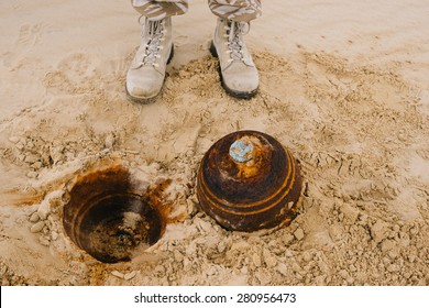 old ammunition demining in the sand, sapper and his feet after ammunition found
