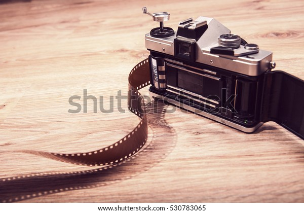 Old analog camera back door and photo film on wood background.  Roll of photographic film. Beautiful vintage design. Photo with Analog design.