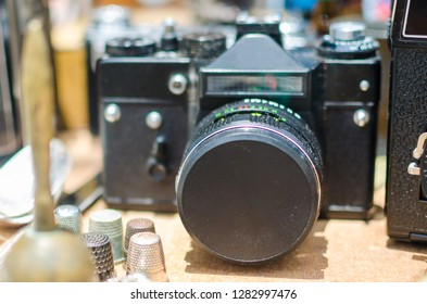 Old analog camera on a wooden table among other retro objects. Vintage backgrounds.