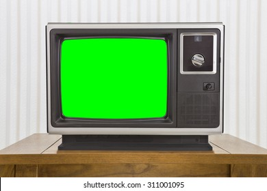 Old analogue portable television on table with green screen.