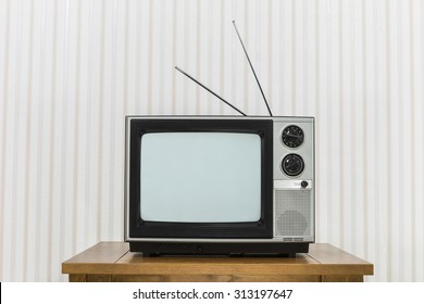 Old analogue television with antenna on wood table