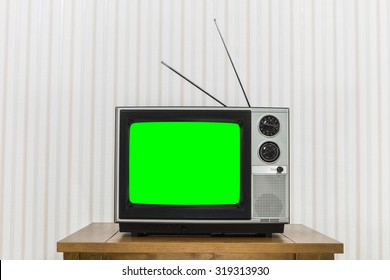 Old analogue television on wood table with chroma key green screen.