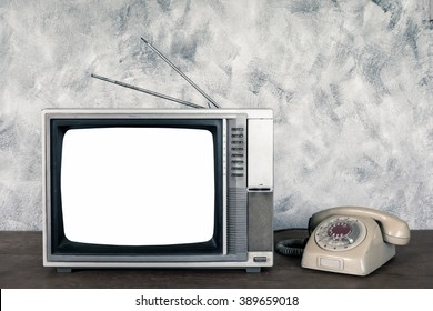 Old analogue television and telephone on wood table with textured background.
