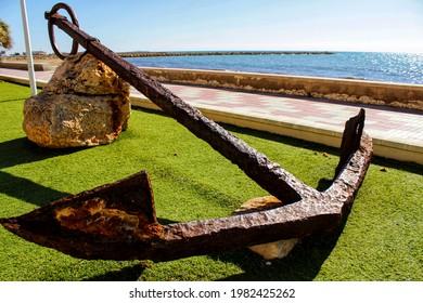 Old anchor on a promenade of Santa Pola, Alicante. Mediterranean sea on background. - Shutterstock ID 1982425262