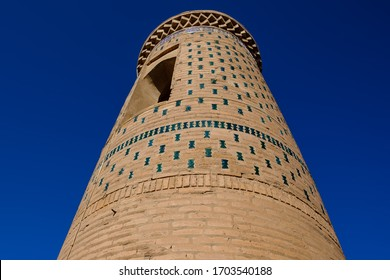 Old ancient minaret with green decor on the sky background. Central Asia travel view.
