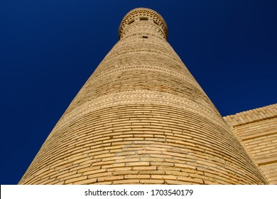 Old ancient minaret on the sky background. Central Asia travel view.