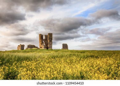 Old ancient ruined church set in a yellow crop landscape with beautiful clouds and sunset sunlight