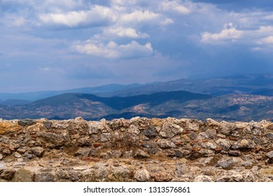 old and ancient stone wall closeup on an indistinct background of a natural landscape