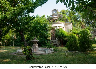 Old ancient white destroyed stone house on the green yard with trees around. Poverty and misery, South, summer