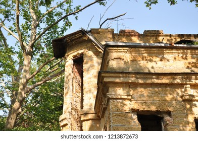 Old ancient yellow destroyed stone house on the yard with trees around. Poverty and misery, South, summer