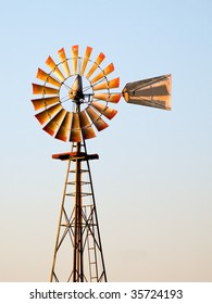 Old antique Aermotor windmill used to pump water for cattle on a ranch or farm lit by warm glow of the setting sun.