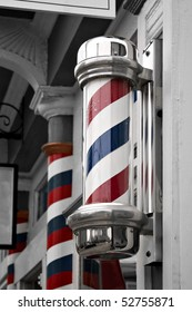 An old antique barber shop pole with red and blue stripes with selective color.