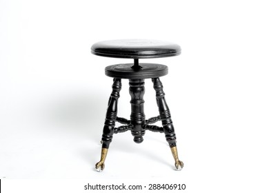 Old antique black stool with a round seat from a piano