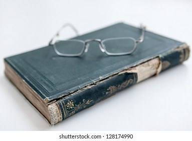 An old antique book with glasses