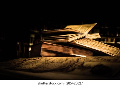 Old antique books on a library desk lit in the dark